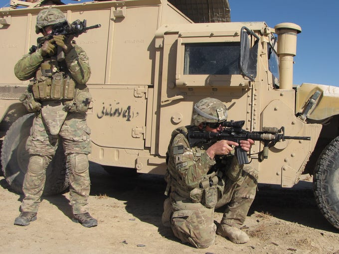U.S. soldiers peer through the scopes of their weapons after being fired upon by unseen assailants following a joint patrol with Afghan forces in a small village in Ghazni.