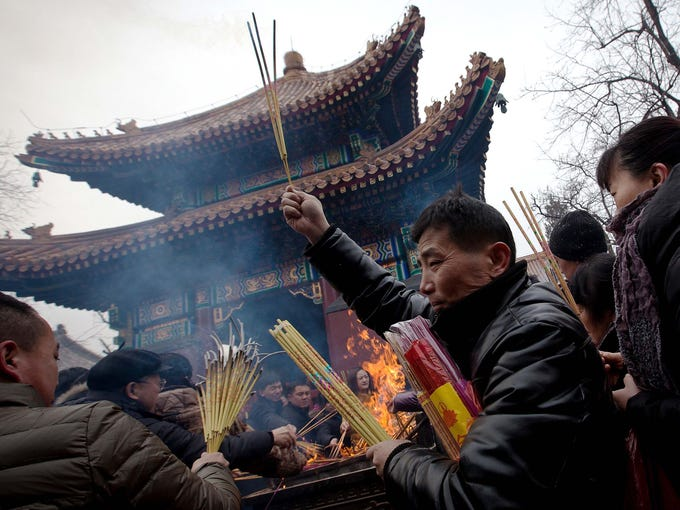A man holding incense makes his way through the crowd to offer prayers for the Chinese Lunar New Year at Yonghegong Lama Temple in Beijing.