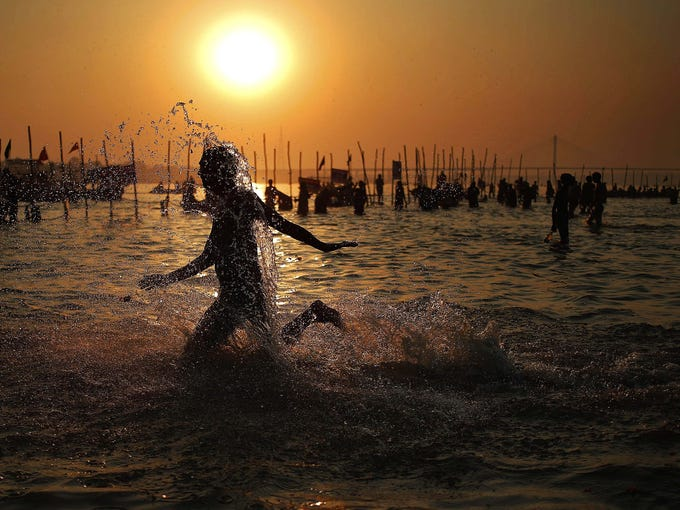 A man runs in the water while bathing at Sangam, the confluence of Hindu holy rivers Ganges, Yamuna and the mythical Saraswati, during the Maha Kumbh festival at Allahabad, India, on Feb. 10.