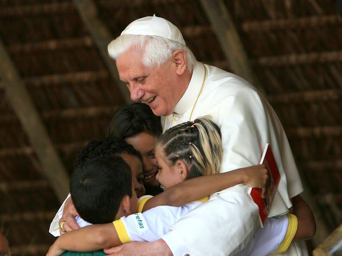 Pope Benedict XVI embraces children during a visit at the Fazenda da Esperanca, a facility for recovering drug addicts, on May 12, 2007, in Guaratingueta, Brazil.