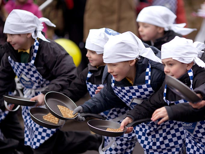 Schoolchildren participate in the annual Shrove Tuesday Women's Trans-Atlantic Pancake Race on Feb. 12 in Olney, England.  Every year women from Olney and the U.S. town of Liberal, Kan., race with a pancake in their pan, flipping it at the beginning and end of the race. Pancakes are associated with Shrove Tuesday because they were a traditional way to use up rich foods such as milk, eggs and sugar before the start of the 40-day fasting season of Lent.