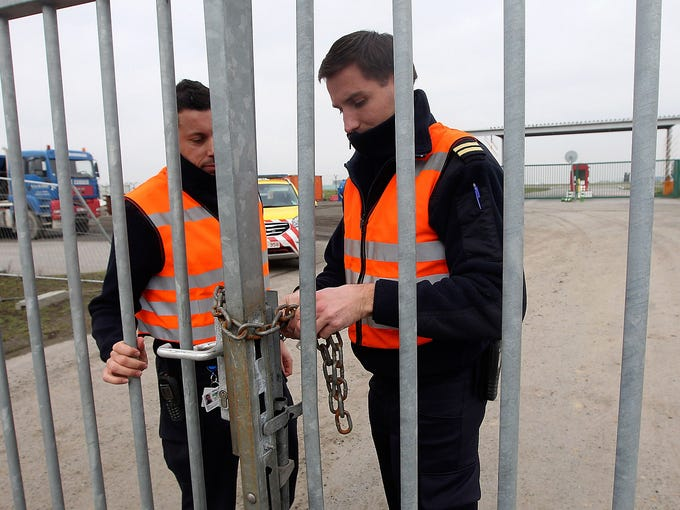 Airport police officers chain a gate leading to the tarmac after thieves stole a shipment of diamonds from a parked aircraft at Brussels Airport on Feb. 19 in Belgium. Eight masked gunmen cut a hole in a security fence, drove onto the tarmac and snatched $50 million worth of uncut diamonds from the hold of a Helvetic Airways jet without firing a shot.