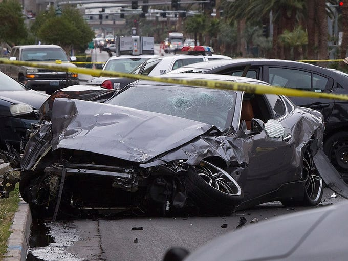 Police tape off the scene of  a shooting and multicar accident on the Las Vegas Strip on Feb. 21 in Las Vegas. Police say three people were killed  when someone in a Range Rover opened fire on people driving a Maserati, sending it crashing into a taxi cab that exploded in flames.