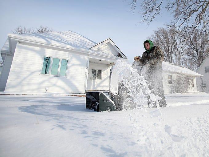 Nolan Driver clears his sidewalk on Feb. 22 in Minden, Iowa.