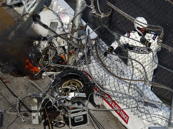 An official stands next to the damaged crash fence as the engine of NASCAR Nationwide Series driver Kyle Larson catches fire during the DRIVE4COPD 300 at Daytona International Speedway.