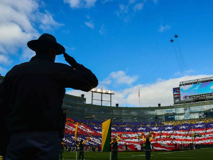A Green Bay police officer salutes during a flyover during the playing of the national anthem before a Packers game at Lambeau Field.