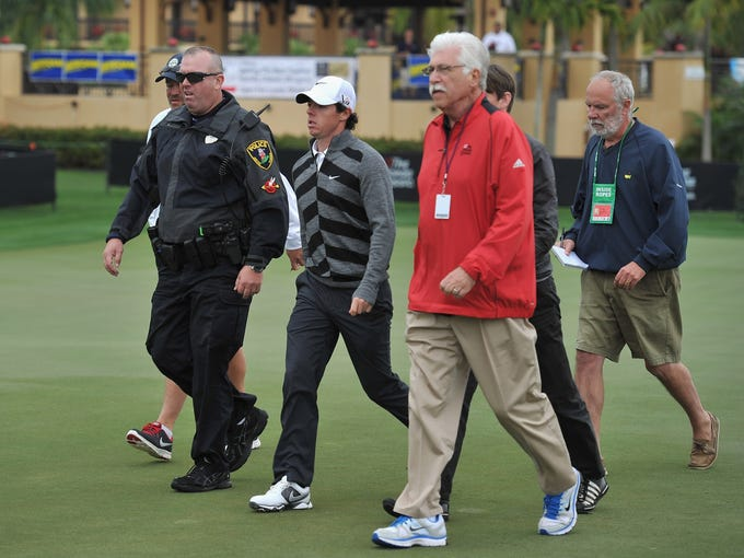 Rory McIlroy of Northern Ireland walks off the course on the 18th hole, headed for the parking lot. The defending champion was 7 over through 8 holes in the second round and withdrew because of wisdom tooth pain.