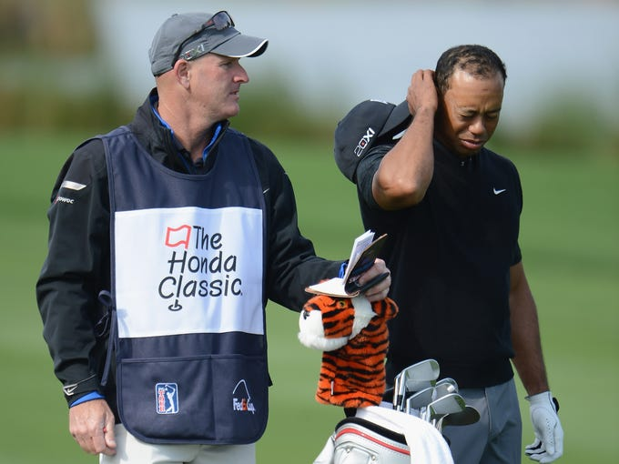 Tiger Woods doesn't look too happy as he ponders how to hit a shot in the third round of the Honda Classic.