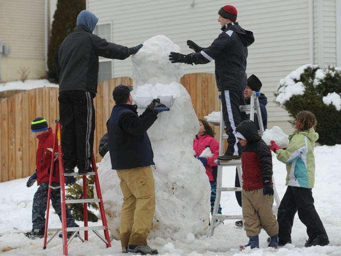 David Sant, left on ladder, and Christian Leigh, right ladder, set the head of a large snowman being built by neighbors on Marquis Court in Stafford County, Va.