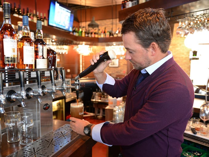 McDowell pours a pint of Guinness.