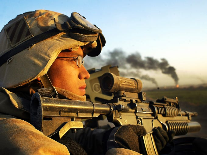 U.S. Army Spc. Mitchell Roe with the 11th Engineer Battalion watches the horizon as destroyed Iraqi artillery positions burn on April 2, 2003, near the Karbala Dam. Ten years ago, a U.S.-led coalition invaded Iraq on March 20, 2003.