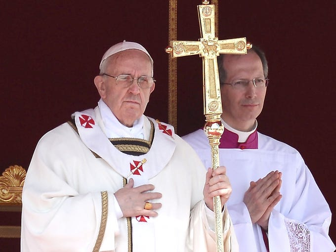 Pope Francis lifts a cross during his inauguration Mass on March 19 at St. Peter's Square at the Vatican.
