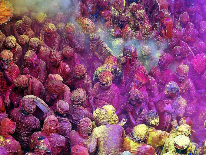 Hindu devotees are covered with colored powder at the Radha Rani Temple during the Lathmar Holi Festival on March 21 in Barsana, India. The festival is held before the national Holi Day event March 27.