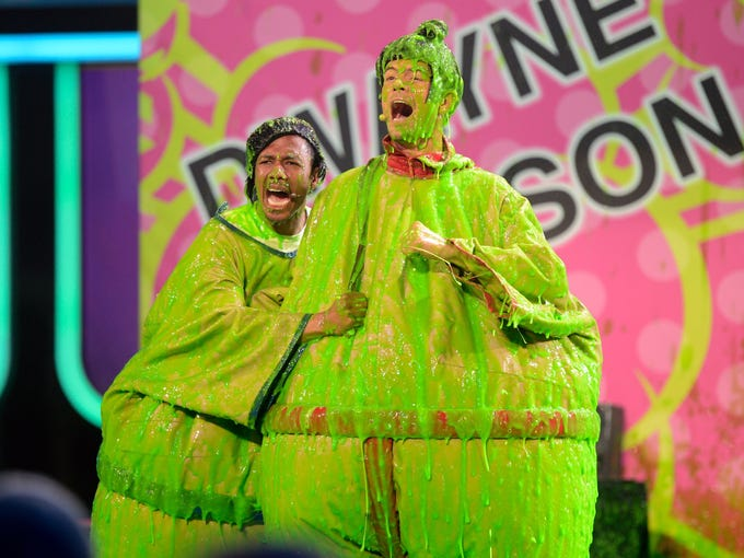 Nick Cannon, left, and  Josh Duhamel  get the big green while hosting Nickelodeon's Kids' Choice Awards on March 23 in Los Angeles.