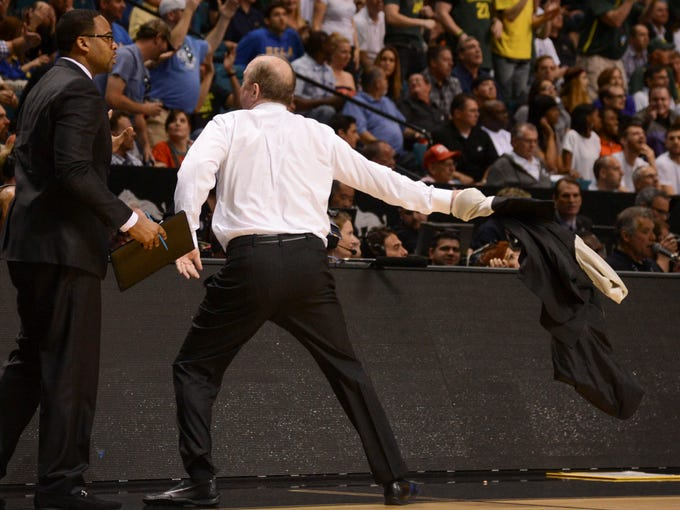 UCLA Bruins head coach Ben Howland (right) throws his jacket into the crowd after a charging call on forward Shabazz Muhammad during the first half of the championship game of the Pac 12 tournament against the Oregon Ducks at the MGM Grand Garden Arena. Howland received a technical foul.