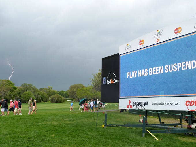 Lightning strikes in the distance as spectators leave the course. A storm with rain, lightning and 40-mph-plus winds whipped through Bay Hill on Sunday and delayed the final round of the Arnold Palmer Invitational.