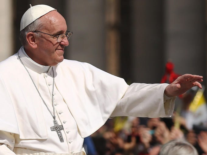 Pope Francis waves to the crowd during a drive around St. Peter's Square after delivering his blessing of the palms and to the faithful gathered during Palm Sunday Mass on March 24 in Vatican City.