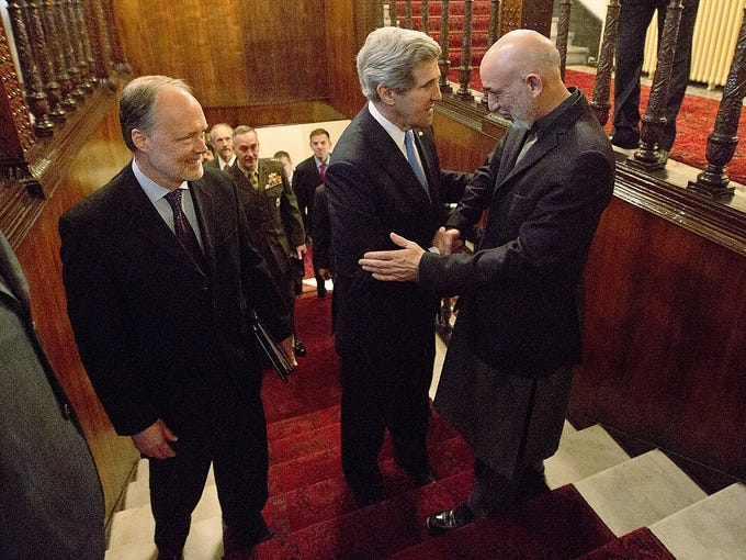 Secretary of State John Kerry, center, shakes hands with Afghan President Hamid Karzai as the U.S. Ambassador to Afghanistan, James Cunningham, watches on March 25 at the Presidential Palace in Kabul. Kerry is in Afghanistan on an unannounced visit to meet with Afghan government officials.