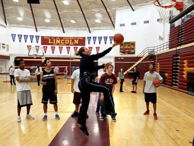 Des Moines Police Department school resource officer Deb VanVelzen makes a layup in the Lincoln High School gym while visiting with student Jordan Sellers, right, during her daily rounds at the school on March 12. For three years, VanVelzen has been Lincoln's first line of defense in major threats and emergencies. She also is called on to head off problems before they escalate.