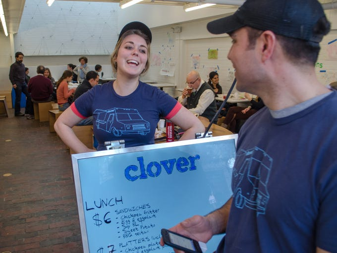 Standing near the electronic menu board, Manager Craig Nelson and Rachel Greenstein wait for entering customers at the Harvard Square location of Clover Food Labs.