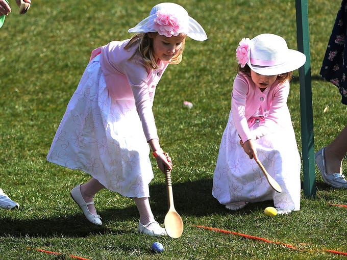 Girls roll colored eggs across the South Lawn during the White House Easter Egg Roll on April 1 in Washington.