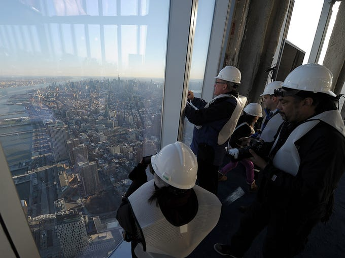 People take photographs of the city as officials open the One World Observatory site to the media at the One World Trade Center tower on April 2 in New York City. The observatory towers 1,250 feet over Manhattan and will open to the public in 2015.