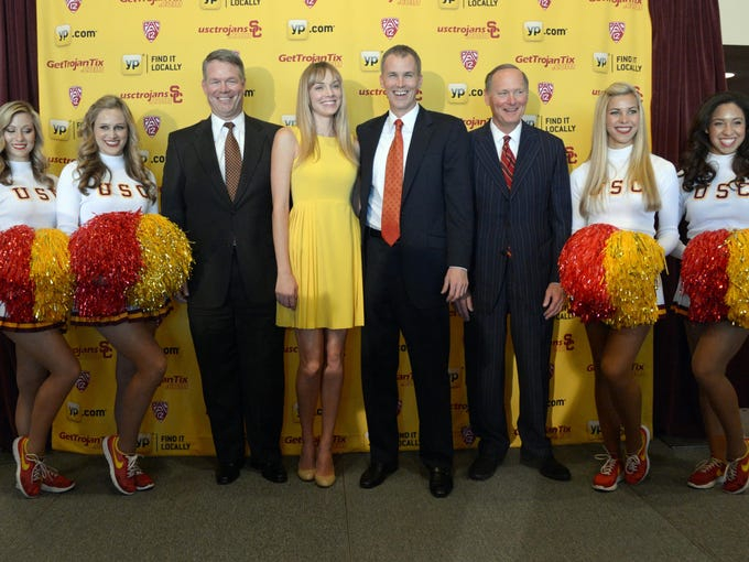 Andy Enfield (center) poses with his wife Amanda Marcum Enfield and Southern California Trojans athletic director Pat Haden (right) and senior associate athletic director Steve Lopes (left) and Song Girls cheerleaders at a press conference April 3.