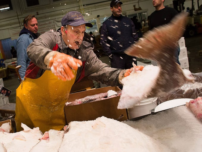 A fishmonger tosses a halibut onto a table on March 29 at the New Fulton Fish Market in New York. Located in the Hunts Point neighborhood of the Bronx, it is the world's largest after Japan's Tsukiji Fish Market in Tokyo.