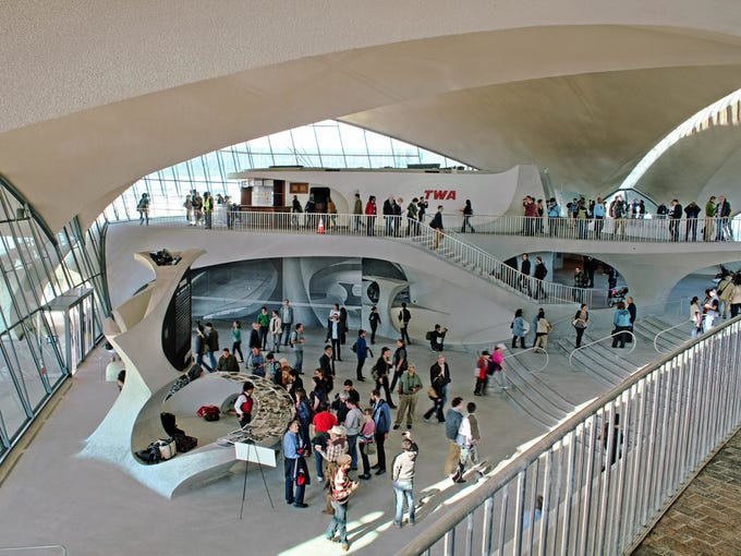 """JFK's Terminal 5, which includes the building formerly called the TWA Flight Center, serves as the airport's JetBlue Terminal.. The space was designed by Finnish American architect Eero Saarinen in 1962, and was meant to look like a seagull in flight. The building's unique design has been used as a New York filming location for movies like """"Catch Me if You Can."""""""