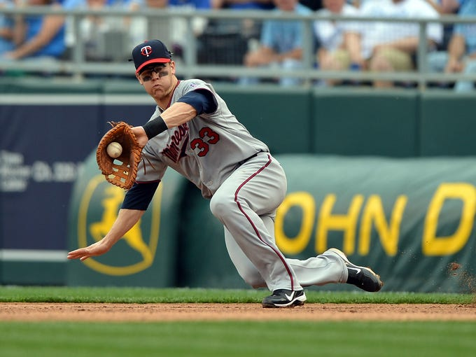 Twins first baseman Justin Morneau fields a ground ball against the Royals.