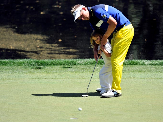 Luke Donald putts with his daughter Elle