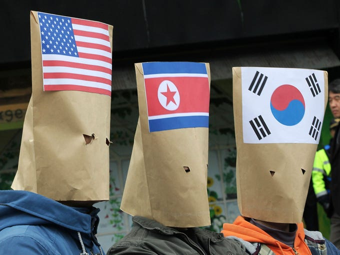 South Korean protesters wear masks with flags of the United States, left, North Korea and South Korea during a Global Day of Action on Military Spending rally near the U.S. Embassy in Seoul. The demonstrators are demanding a peaceful reunification of the Korean peninsula.