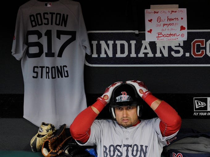 Boston Red Sox right fielder Shane Victorino (18) puts on his helmet before a game against the Cleveland Indians at Progressive Field. A Red Sox jersey with the Boston area code was hung in the dugout along with a note from a Cleveland fan.