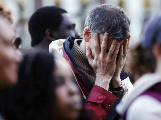 A mourner reacts during a candlelight vigil held at the Cambridge, Mass., City Hall.
