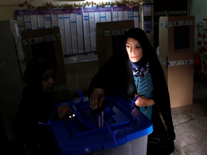 An Iraqi woman, the last voter in a Karrada neighborhood polling center, casts her ballot Saturday, April 20, in provincial elections in Baghdad. Iraqis passed through security checkpoints and razor-wire cordons to vote in the country's first election since the U.S. military withdrawal, marking an important test of the country's stability.