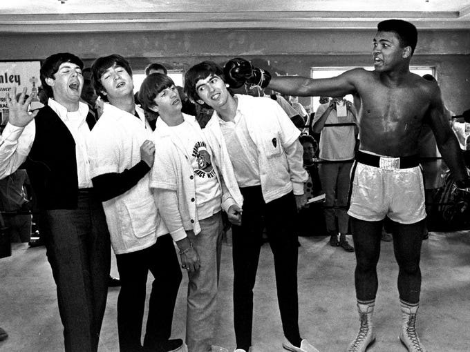 In this Feb. 18, 1964, file photo, The Beatles -- from left, Paul McCartney, John Lennon, Ringo Starr, and George Harrison -- take a fake blow from Cassius Clay, who later changed his name to Muhammad Ali, while visiting the heavyweight contender at his training camp in Miami Beach, Fla.