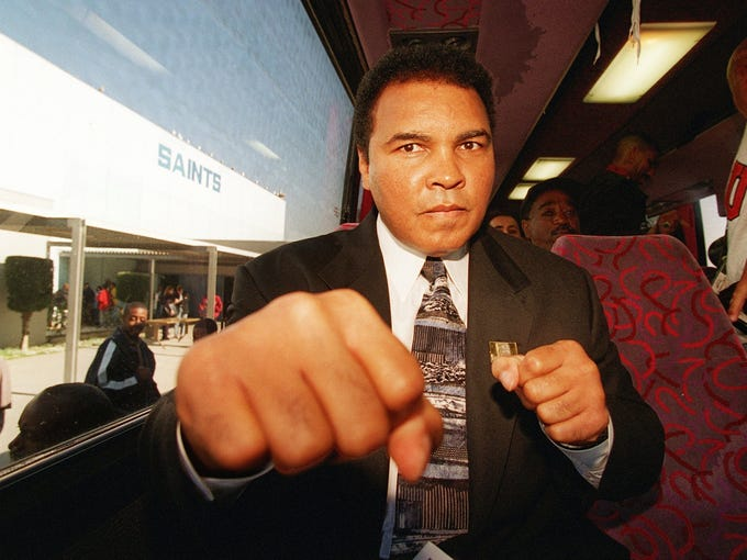 Muhammad Ali playfully spars with a photographer while on a tour bus to visit Alain Leroy Locke High School on Dec. 3, 1996, in South-Central Los Angeles.