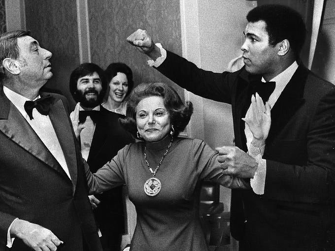 "At a dinner honoring the six ""Outstanding Chicagoans of Today,"" boxing champ Muhammad Ali takes a playful poke at sportscaster Howard Cosell, as Ann Landers advises them to break it up on Nov. 11, 1977."