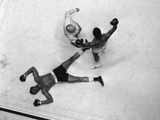 Cleveland Williams is spread eagled on the canvas as referee Harry Kessler sends Cassius Clay to a neutral corner during their heavyweight bout at the Astrodome in Houston, in this Nov. 14, 1966 photo.
