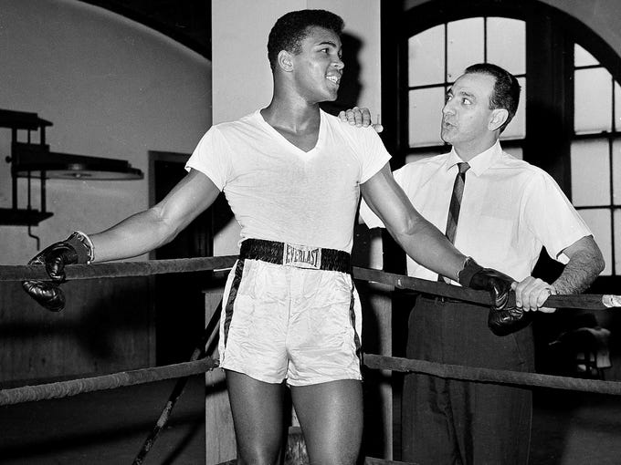 In this Feb. 8, 1962, file photo, young heavyweight fighter Cassius Clay, who later changed his name to Muhammad Ali, is seen with his trainer, Angelo Dundee, at City Parks Gym in New York.