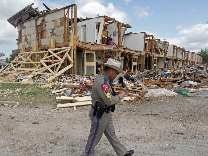 Texas Department of Public Safety Sgt. Jason Reyes walks past a damaged apartment complex four days after an explosion at a fertilizer plant in West, Texas.