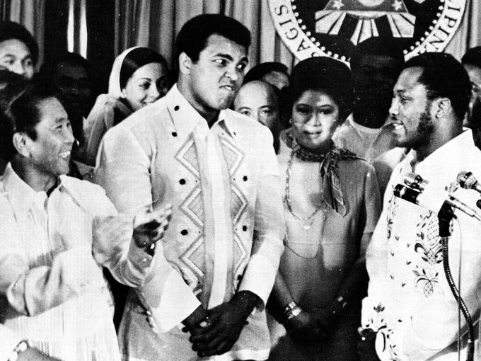 Philippines President Ferdinand Marcos, left, applauds as challenger Joe Frazier, right, makes some remarks about world champion Muhammad Ali, second from left, during their call on Marcos at the Malacanang Palace in Manila, Sept. 18, 1975.