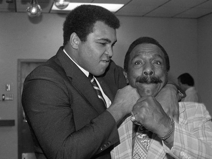 Former heavyweight champion Muhammad Ali delivers a friendly punch to his father, Cassius Clay, Sr., during a news conference, Jan. 4, 1980, in Los Angeles.