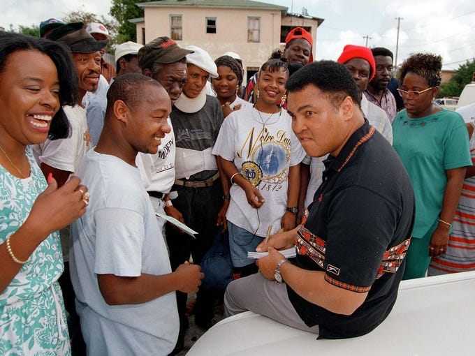 Muhammad Ali signing autographs and teasing friends in Overtown Neighborhood, Miami, Fla., in 1994.
