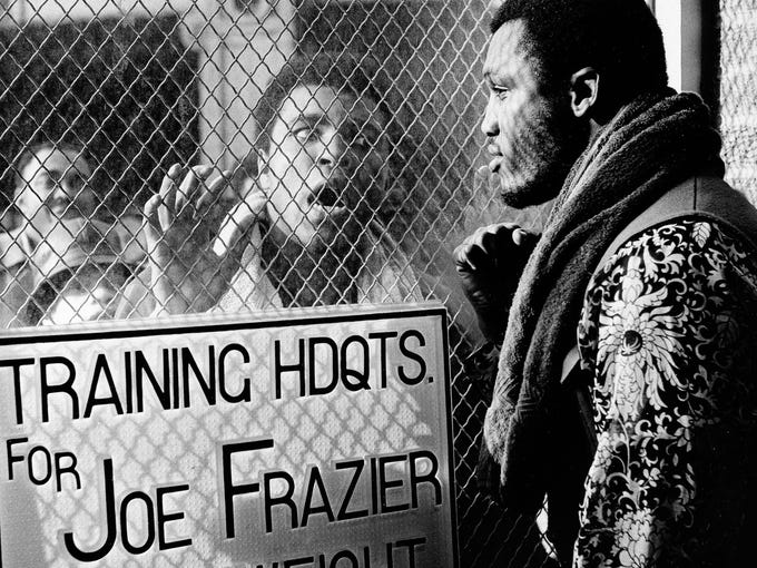 Former heavyweight champ Muhammad Ali appears outside champ Joe Frazier's gym in Philadelphia, Jan. 28, 1971, before the two were scheduled for a bout at New York's Madison Square Garden in March.