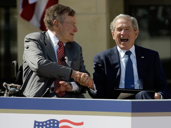 Former president George H.W. Bush shakes hands with his son, former president George W. Bush, on April 25 at the dedication of the George W. Bush Presidential Center on the campus of Southern Methodist University in Dallas.