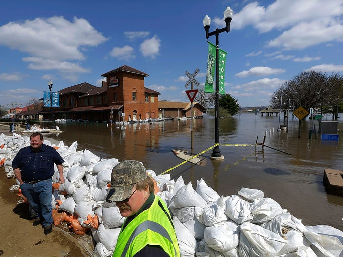 Volunteers and government officials monitor the sand bag wall holding back the Illinois River on April 24 in Peoria, Ill.