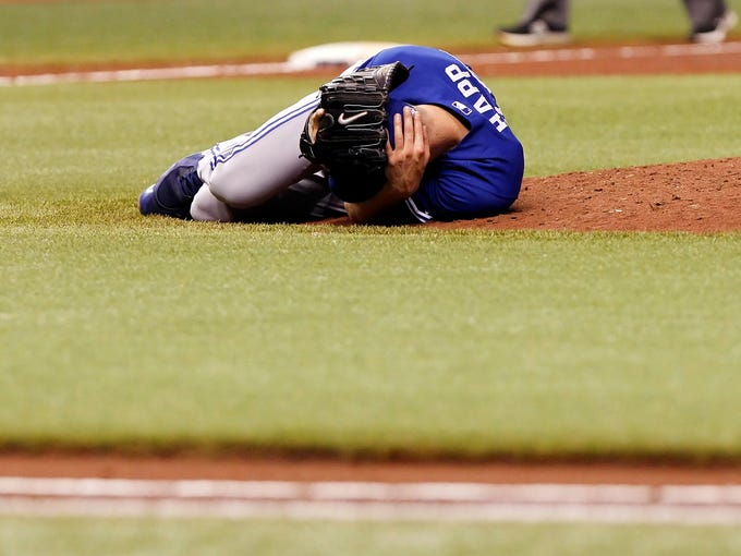 Toronto Blue Jays starting pitcher J.A. Happ falls to the ground and grabs his head after he was hit by a line drive hit by Tampa Bay Rays' Desmond Jennings.