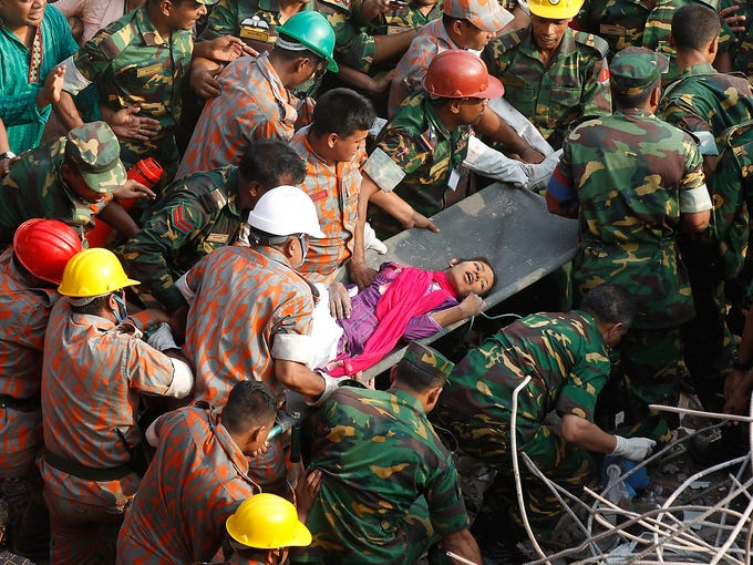 Rescuers evacuate a garment worker from the rubble of a collapsed building on May 10 in Savar, Bangladesh. The woman was rescued after spending 17 days buried under the rubble of a collapsed eight-story garment factory.