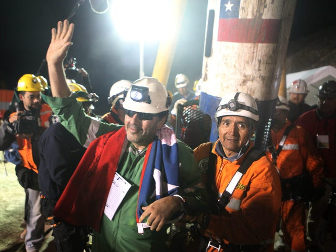 Luis Urzua, waves after being freed on Oct. 13, 2010, from the collapsed San Jose gold and copper mine where he had been trapped with 32 other miners for over two months near Copiapo, Chile. The 69-day underground ordeal reached its end after 33 trapped miners were hauled up in a cage through a narrow hole drilled through 2,000 feet of rock.